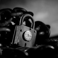 black and white photo of an antique combination pad lock, sitting in a pool of chains