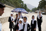 A group of young school girls watch a demonstration pass organized by women's rights group Young Women for Change in the streets of Kabul. Afghanistan, 2012