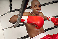 Boxer in red boxing gloves resting at side of ring