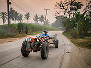 09 FEBRUARY 2015 - THA MAI, KANCHANABURI, THAILAND:  A farmer drives his tractor on a country road lined with sugarcane fields. Thailand is the world's second leading sugar exporter after Brazil. The 2015 sugarcane harvest in Thailand is expected to fall about 5% compared to the 2014 harvest because of a continuing drought in Southeast Asia. Brazilian production is also expected to fall this year because of ongoing drought in Brazil. Australia, the number 3 sugar exporter, is also expected to see a smaller harvest this year because of continuing draught in Australia.  PHOTO BY JACK KURTZ