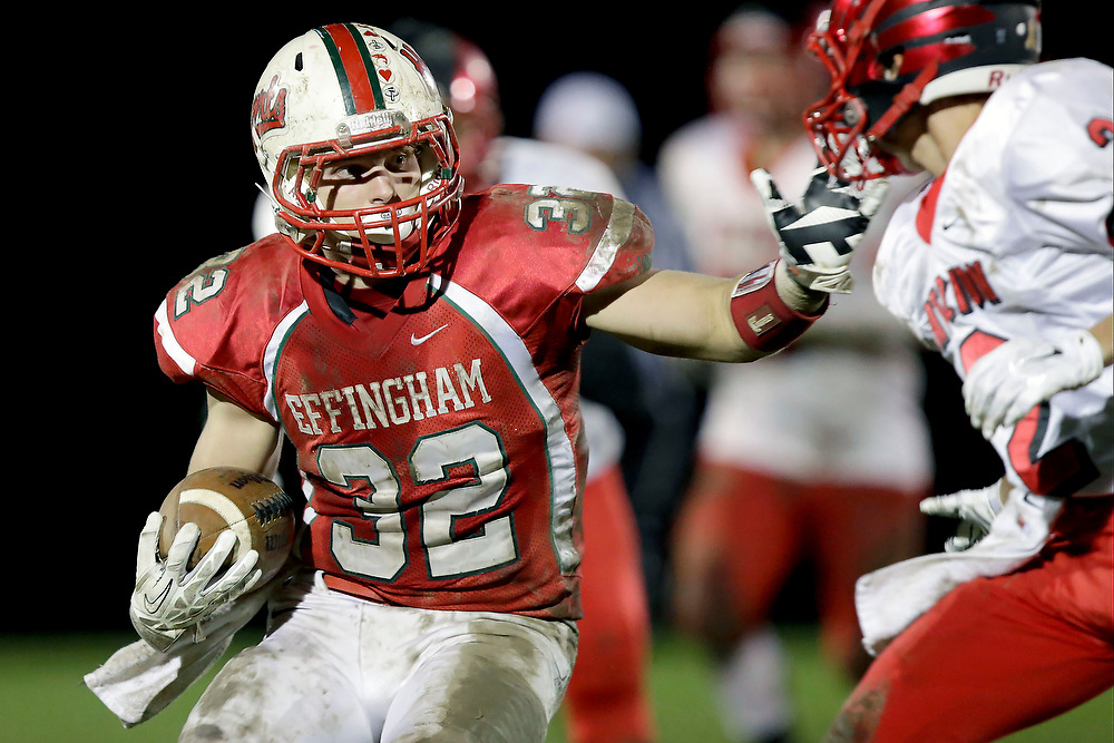 Effingham's Zach Miller (32) runs the ball against the defense of Mt. Zion's Charles Kuhle (2) during the first half of a game at Effingham High School's Klosterman Field Friday, Oct. 17, 2014, in Effingham, Ill. (Herald & Review/ Stephen Haas)