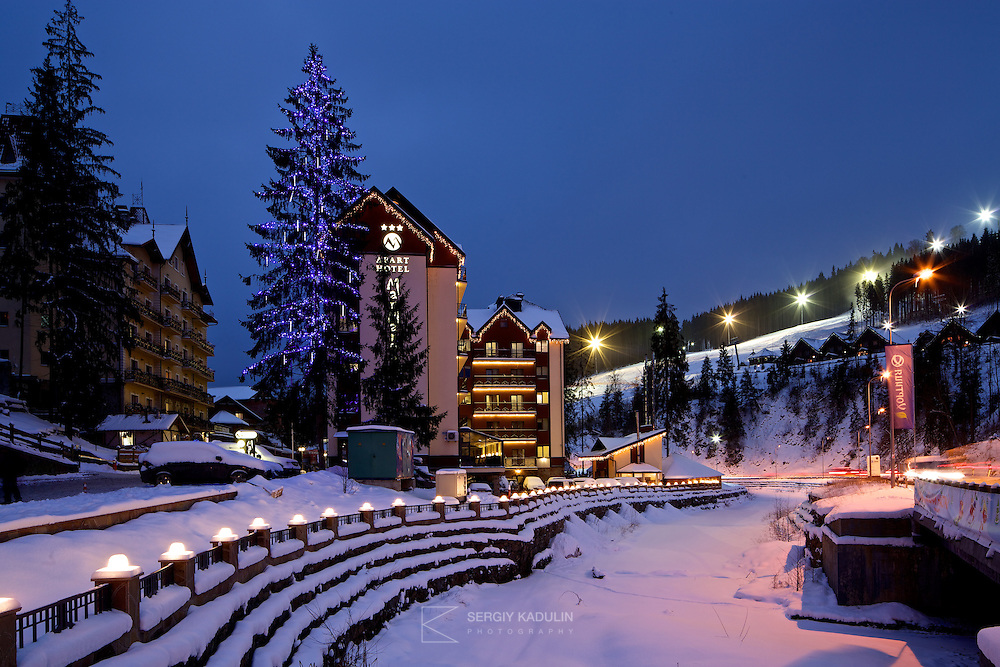 Evening view of Apart Hotel at Bukovel skiing resort, Ukraine. Hotel building decorated with Christmas lights. Skiing slope with lights on the background.