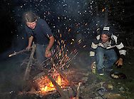 Austin Chantry throws on more wood as Carlos Vargas fears ash will ruin the chicken he cooked in a cast iron skillet on the campfire Saturday night camping in upper Flat Creek.