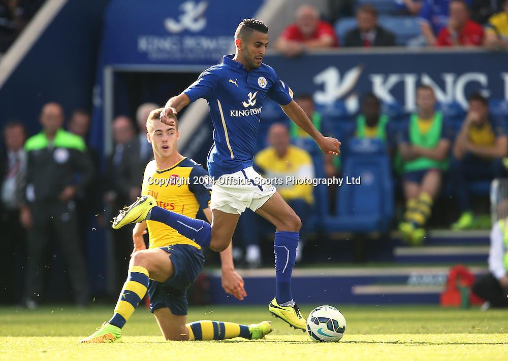31 August 2014 Premier League football Leicester City v Arsenal - Riyad Mahrez of Leicester skips over the tackle of Calum Chambers.<br /> Photo: Mark Leech