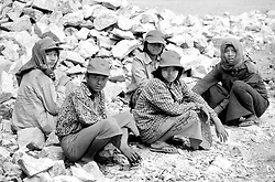BURMA (MYANMAR) Yangon Division, Thanlyin. These rock breakers paused for only a moment during their punishingly difficult work. It is common to find women  and young men like these on road crews.