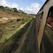 "Passengers watch the scenery from their cabins on the train from Nairobi to Mombasa. Also known as the ""Lunatic Express"", It was the railway line that built Kenya, linking the port town of Mombasa through the capital, Nairobi, to the shores of Lake Victoria and on to the Ugandan capital, Kampala. It cost $5m (in 1894 money) and countless workers died during its construction. There were derailments, collisions, tribal raids and attacks by lions. Yet despite becoming one of Kenya's national treasures and a vital economic artery for east Africa, the railway now lies in a state of disrepair. A South African consortium has taken it over and plans to invest millions, returning it to its former glory. But there has been a row over the railway's financing which may yet derail the .project. .."