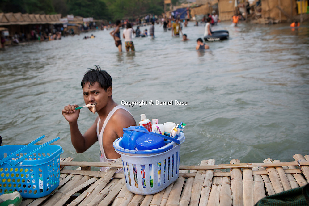 A man brushing his teeth in the same river they bathe in. Shwet Set Taw, Magwai Division, Myanmar. February 2014.