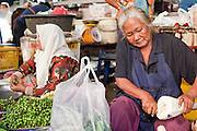 """Sept 25, 2009 -- PATTANI, THAILAND: Muslim women (left) and a Thai Buddhist woman work as vendors in the morning market in Pattani, Thailand. Thailand's three southern most provinces; Yala, Pattani and Narathiwat are often called """"restive"""" and a decades long Muslim insurgency has gained traction recently. Nearly 4,000 people have been killed since 2004. The three southern provinces are under emergency control and there are more than 60,000 Thai military, police and paramilitary militia forces trying to keep the peace battling insurgents who favor car bombs and assassination.  Photo by Jack Kurtz / ZUMA Press"""