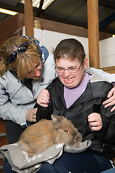Young woman with learning disabilities on a trip to an animal centre unsure about stroking a large pet rabbit,