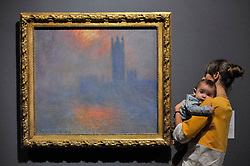 "© Licensed to London News Pictures. 30/10/2017. London, UK.  A visitor views ""Houses of Parliament, Sunlight Effect in the Fog"", 1904, by Claude Monet at a preview of ""Impressionists in London, French Artists in Exile (1870-1904)"" at Tate Britain.  The exhibition brings together over 100 works by Monet, Tissot, Pissarro and others in the first scale show of French artists who sought refuge in Britain during the Franco-Prussian War and shows views of London as seen through French eyes.  The exhibition runs 2 November 2017 to 29 April 2018.  Photo credit: Stephen Chung/LNP"