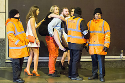 © Licensed to London News Pictures . 01/01/2015 . Manchester , UK . A man gives a woman a piggy back ride to the taxi queue . Revellers usher in the New Year on a night out in Manchester City Centre .  Photo credit : Joel Goodman/LNP