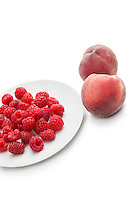 Raspberries in plate with peaches over white background