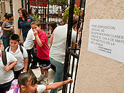 Apr. 27, 2009 -- NOGALES, SONORA, MEXICO: School children in Nogales, Sonora, Mexico, walk past a sign announcing school is closed until at least May 6 because of the outbreak of swine flu. The Mexican government broadened its efforts to control the outbreak of swine flu Monday closing schools throughout the country. In Nogales, on Mexico's northern border with the US, people started wearing masks as news of the outbreak spread.  Photo by Jack Kurtz