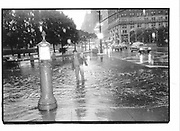 Man crossing flooded road. 58st and 5 Ave, Sunday ,New York.  31 May 1992. © Copyright Photograph by Dafydd Jones 66 Stockwell Park Rd. London SW9 0DA Tel 020 7733 0108 www.dafjones.com