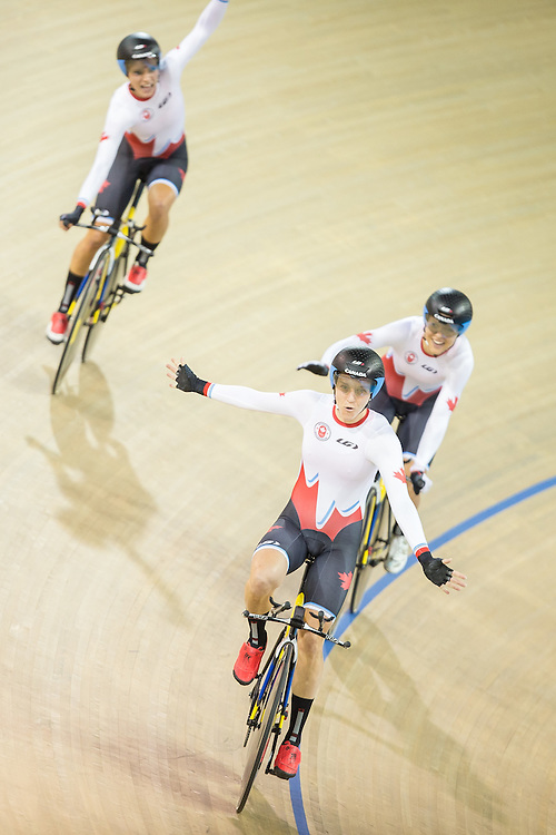 Laura Brown (C) of Canada celebrates her team's gold medal win in the women's cycling team pursuit with teammates Jasmin Glaesser (L) and Kirsti Lay at  at the 2015 Pan American Games in Toronto, Canada, July 17,  2015.  AFP PHOTO/GEOFF ROBINS