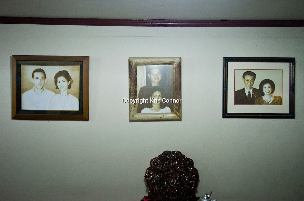 A group of family portraits hangs on a wall in a home in Chiang Mai, Thailand. Photo by Kris Connor