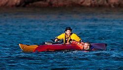 Richard Harpham helps Iain back into his boat after capsizing. Scottish Sun sports editor Iain King takes part in a practise session for his charity kayak challenge, in the waters of the harbour at St Abbs..Pic © Michael Schofield...