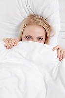 Portrait of young woman covering face with bed sheet
