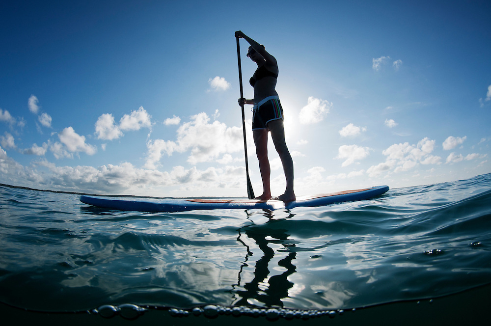 Female paddle boarding on the ocean.