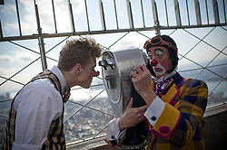 ".---.New York, NY: Mar 04, 2011: .Ringling Bros. and Barnum & Bailey clowns create ""Clown Alley"" in Herald Square. (converge on pedestrians who are able to watch the transformation.) They then walked to Empire State Building and pose for photos on the observation deck..---.Credit: Rob Bennett for The Wall Street Journal.Slug: NYCOVERAGE_Clowns.---."