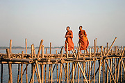 Two Buddhist monks wearing orange safron robes are walking on a bamboo bridge on the Mekong river in Kampong Cham, Cambodia.