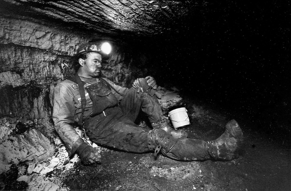 One of the Kline boys takes a break in a low coal mine in West Virginia.