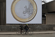 Cyclists pedal past a giant Euro coin, an artwork by Danish artists Superflex, hanging from the hayward Gallery on Waterloo Bridge, on 3rd February 2017, London, England. For the third Waterloo Billboard Commission, the work is a euro coin with its value conspicuously absent – made by the group in 2012, in response to the Greek financial crisis – has gained new resonance since the UK's decision to leave the EU. The billboard is the third in a series of large-scale commissions by international artists, occupying the prominent billboard site next to Hayward Gallery.