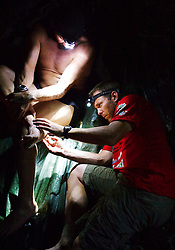 "© Licensed to London News Pictures. 11/10/2013. BRAZIL. Medic treating athletes foot with an injection late into the night after a gruelling day. With no lights in the camp they can only use head lights. Competitors take part in the Jungle Marathon 2013, the ""The toughest ultra marathon in the world"" The race is 245 km long through the biggest jungle in the world, The Amazon. It attracts competitors from all countries world wide. Competitors run through territories of indigenous tribes throughout the 7 day race, where they stay with them as guests.. Photo credit : Alexander Beer/LNP"