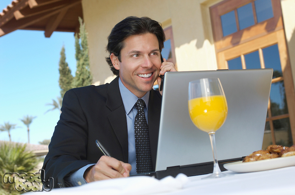 Business man talking on phone and writing in front of laptop, outdoors