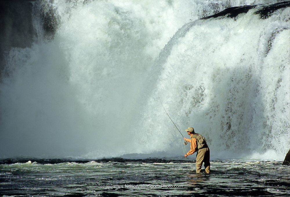 08929-C. An angler casts a fly for trout at the base of Lower Mesa Falls on the Henry's Fork of the Snake River, Idaho.