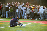 Freedom Plains, NY - A Horace Greeley boys' soccer player sits on the field as Arlington High School players and fans celebrate their 1-0  overtime victory in the Section 1 Class AA championship game on Nov. 7, 2009.