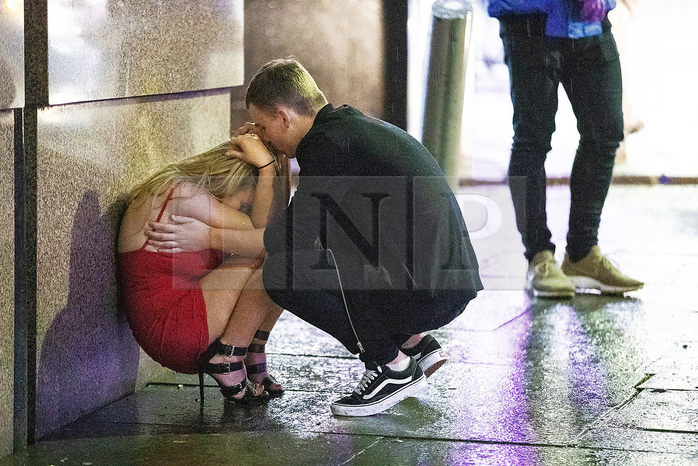 """© Licensed to London News Pictures . 22/12/2018 . Manchester , UK . A man comforts a woman after a fight breaks out outside The Birdcage nightclub on Withy Grove . Revellers out in Manchester City Centre overnight during """" Mad Friday """" , named for historically being one of the busiest nights of the year for the emergency services in the UK . Photo credit : Joel Goodman/LNP"""