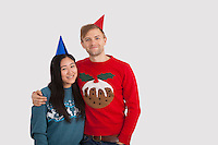 Portrait of happy multiethnic couple wearing party hats at home