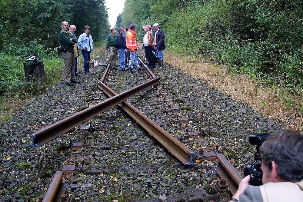 Unbekannte haben auf der Castortransportstrecke zwischen Lüneburg und Dannenberg zwei Gleisstücke herausgeschweisst und zu einem X gelegt. Polizisten begutachten den Schaden.