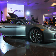 The new 2014 Porsche Cayman S sits in the middle of the showroom floor during the Porsche Cayman S Unveiling event Thursday, May. 2, 2013, at Porsche of Delaware in Newark Delaware.