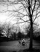 A bicyclist rides through a park near the Eiffel tower in Paris, France.