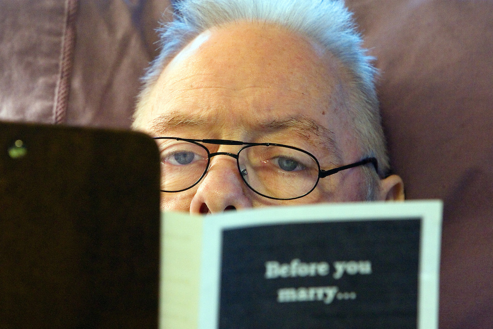 May 5 -- Dick reads over a pamphlet detailing the responsibilities of marriage and medical precautions before signing paperwork for a marriage license. Hospice of North Idaho arranged for Kootenai County clerks to do an in-home visit in order to finalize the forms.