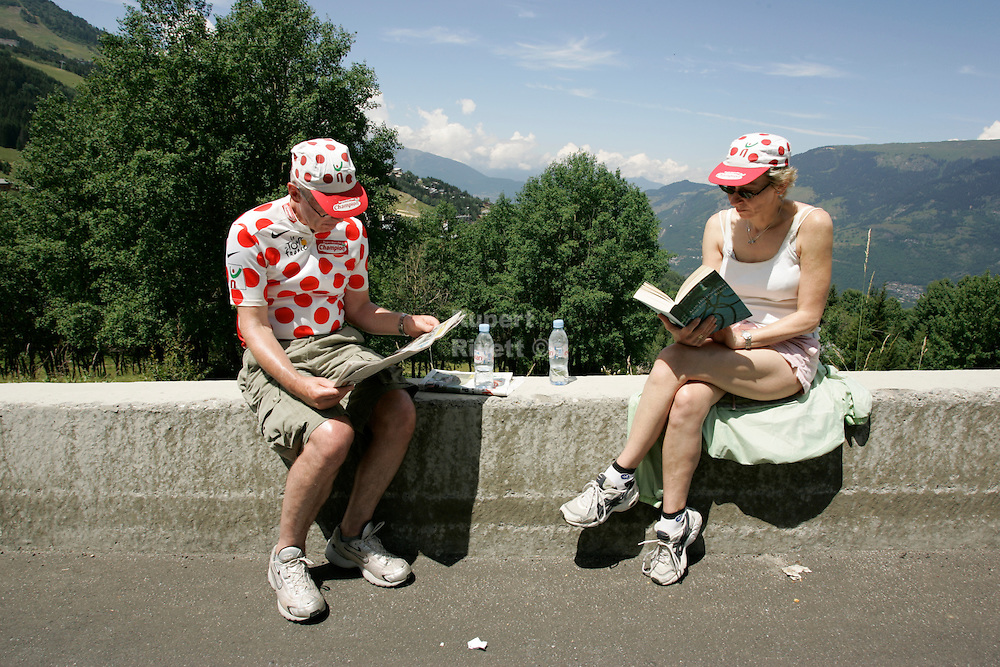 Spectators in their freebie polka dot t-shirt read while they wait for the Tour de France to turn up.