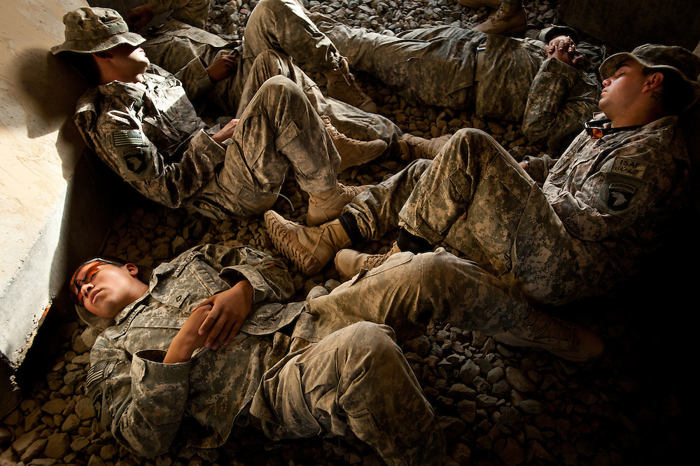 Soldiers rest in a concrete shelter during a mortar attack on Combat Outpost Terminator.