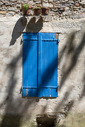 Closed blue shutters and shadows from pots and overhead trees of a village house, on 25th May, 2017, in Lagrasse, Languedoc-Rousillon, south of France. Lagrasse is listed as one of France's most beautiful villages and lies on the famous Route 20 wine route in the Basses-Corbieres region dating to the 13th century.