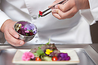 Mid- adult chef arranges edible flowers on salad