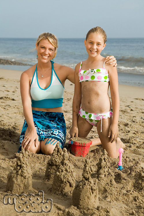 Mother and Young Daughter Building Sand Castle on Beach