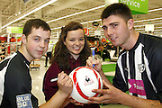 Corby town players l-r, Aiden Ashton and Paul Malone, sign footballs for ASDA corby Sporting Chance Nominee, Lydia Barnham, 16. at the realunch of ASDA in Corby