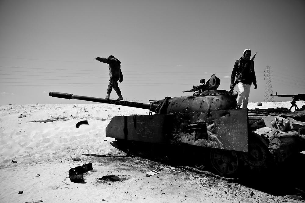 Des combattants rebelles fouillent un char kaddhafiste détruit par les avions de l'OTAN, le 23 mars 2011 à une dizaine de kilomètres d'Aj Dabiya sur la ligne de front.