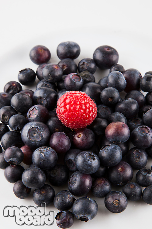 Close-up of raspberry over blueberries against white background