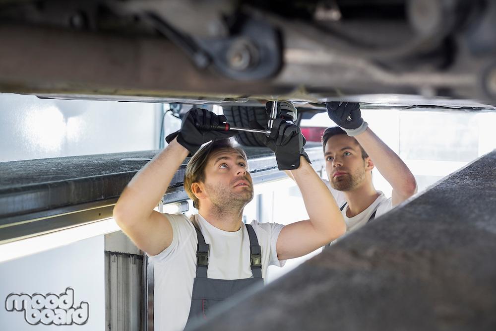 Maintenance engineers repairing car in workshop