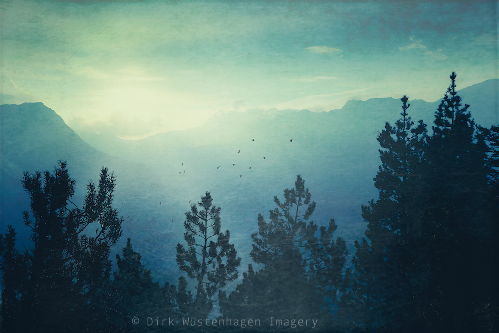 Rising sun in the Alps on a hazy summer morning - texturized photograph