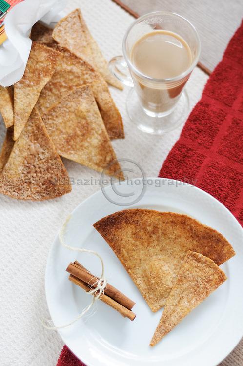 Cinnamon tortilla crisps with cinnamon sticks on white serving plate