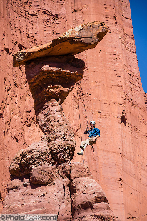 A climber rappels from a hoodoo. The impressive Fisher Towers are eroded from Cutler sandstone capped with Moenkopi sandstone, on BLM federal land near Moab, Utah, USA. Hike the Fisher Towers Trail 4.5 miles round trip with 800 feet gain. The Bureau of Land Management (BLM) is an agency within the United States Department of the Interior that administers American public lands.