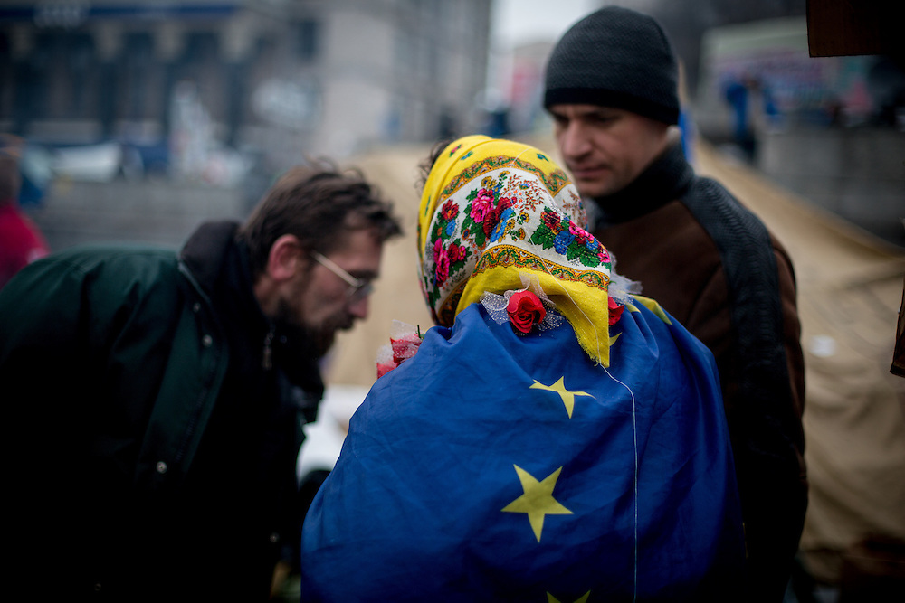 An old woman wears a Russian traditionnal veil on her head and a European flag on her shoulders.